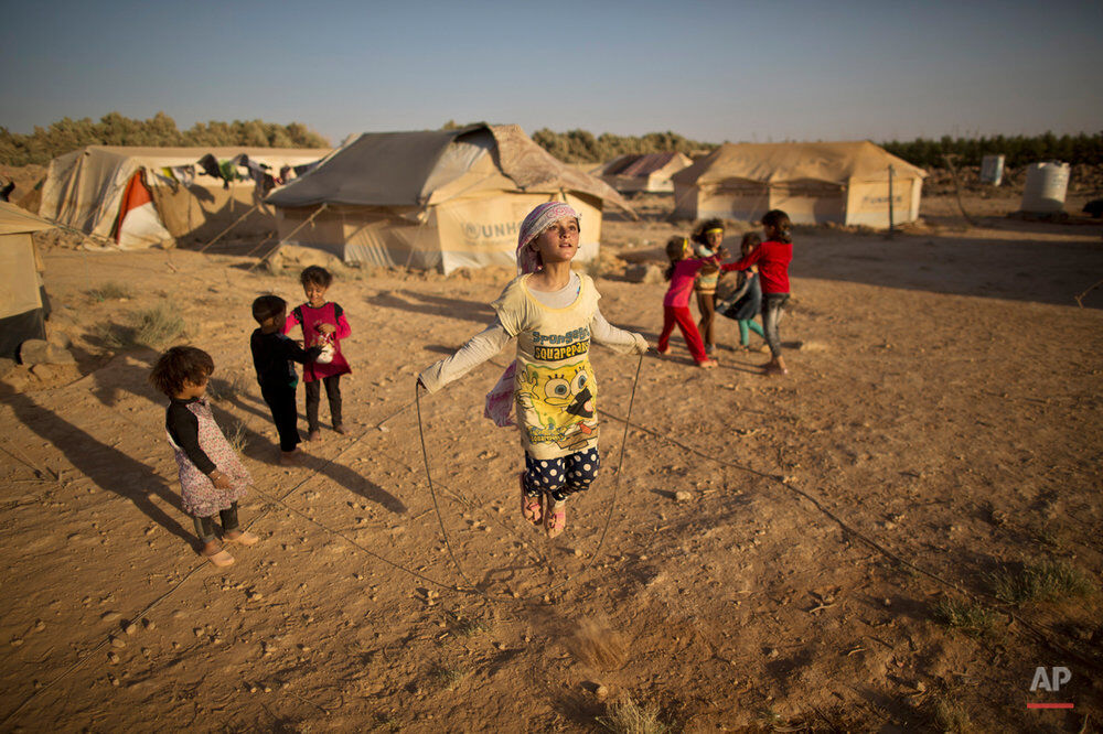 Syrian refugee girl, Zubaida Faisal, 10, skips a rope while she and other children play near their tents at an informal tented settlement near the Syrian border on the outskirts of Mafraq, Jordan, Sunday, July 19, 2015. (AP Photo/Muhammed Muheisen)