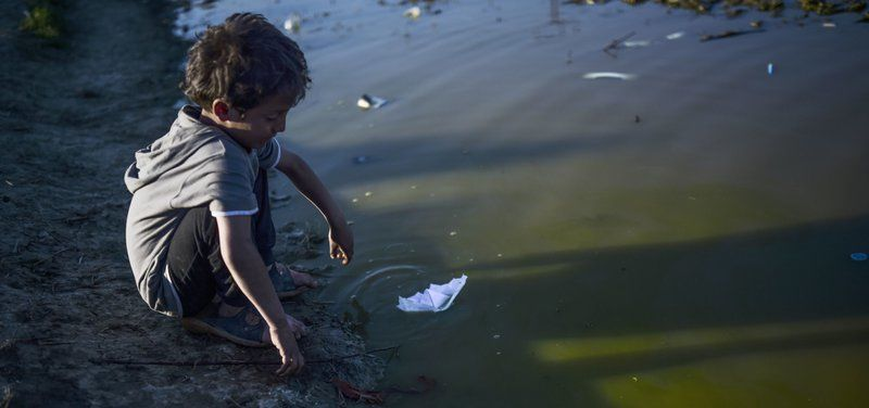 A refugee boy plays with a paper boat at the makeshift camp of the Greek-Macedonian border, near the Greek village of Idomeni on March 31, 2016, where thousands of refugees and migrants are stranded by the Balkan border blockade.  UN chief Ban Ki-moon on March 30 called for a united global effort to tackle the Syrian refugee crisis, as he opened a conference on securing resettlement places for nearly half a million of those displaced. More than one million migrants -- about half of them Syrians -- reached Europe via the Mediterranean last year, a rate of arrivals that has continued through the first three months of 2016. / AFP PHOTO / BULENT KILIC 4638#Agencia AFP
